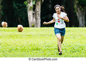 Woman running with Pomeranian dog on green grass in the garden