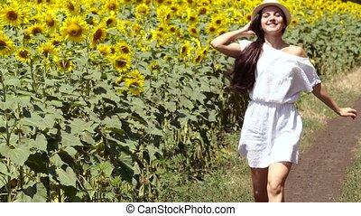 woman runs across the road near a field of sunflowers