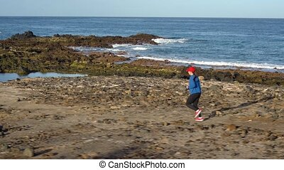 Woman runs along the stony shore of the ocean. Healthy...