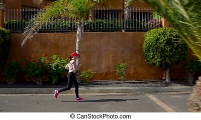 Woman runs down the street among the palm trees. Healthy...