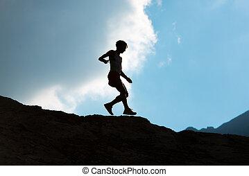 Woman runs downhill on mountain trail