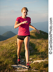 Woman runs on a top of the mountains with mountain range in background