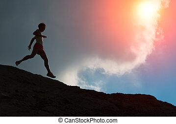 Woman runs on the ridge with colorful sun