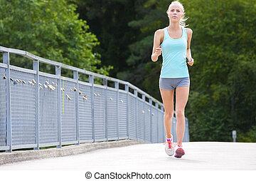 Woman runs outdoor on a bridge as stamina training