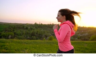 Woman runs outdoors at sunset, slow motion
