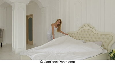 woman runs the linen on the bed man hug her couple home...