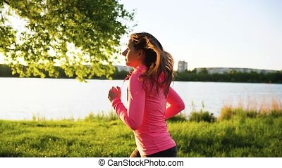 Woman runs through the park on the lake shore at sunset, slow motion