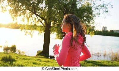 Woman runs through the park on the lake shore at sunset