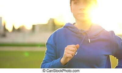 Woman runs through the stadium at sunset - Young woman runs...