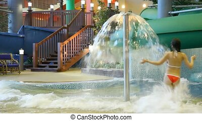 woman runs under fountain in a pool in indoor water park -...