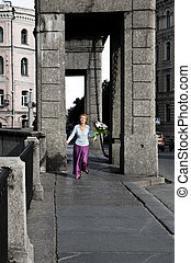 woman  runs with Bouquet through bridge over the river