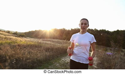woman runs with dumbbells