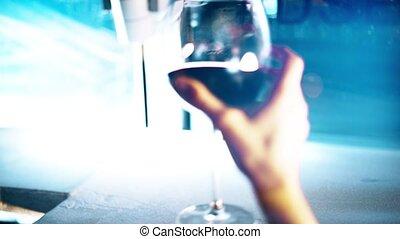 Woman s hand putting a glass of wine on a windowsill at night