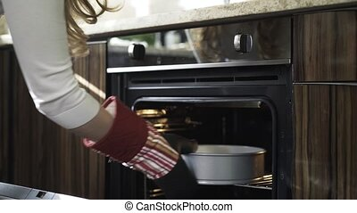 Woman s hand putting dough to oven