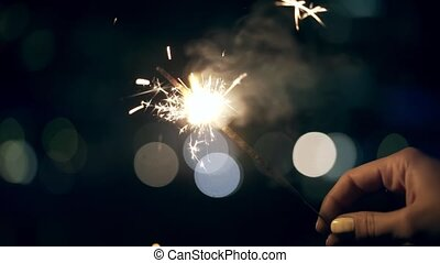 Woman s hands holding a sparkler at night