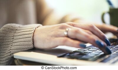Woman s hands with blue nail polish typing at laptop, pan shot