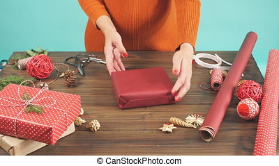 Woman s hands wrapping Christmas gift on dark wooden...