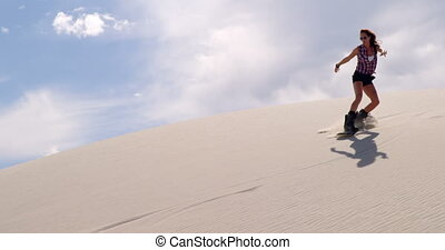 Woman sand boarding on the slope in desert 4k - Woman sand...