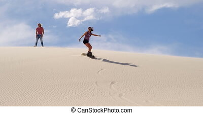 Woman sand boarding while man watching her 4k