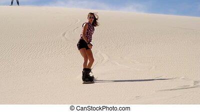 Woman sand boarding while man watching her 4k - Woman sand...