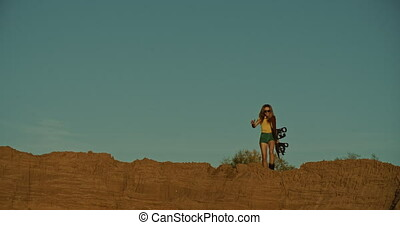 woman sandboarder on a cliff, sunset light - Tourists Sand...