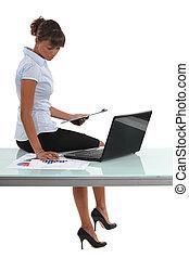Woman sat at desk looking at graphs