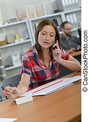 Woman sat at desk, on telephone