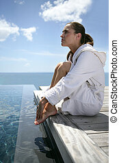Woman sat at the end of a jetty