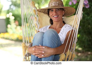 Woman sat in a hammock
