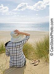 woman sat on beach