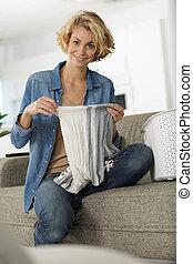 woman sat on the sofa folding laundry