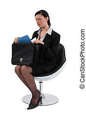 Woman sat removing document from briefcase