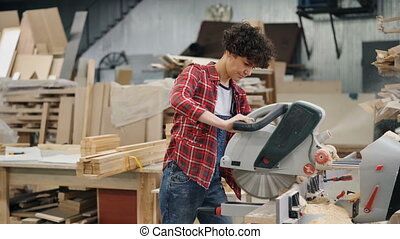 Woman sawing wood in workshop using electric saw working...