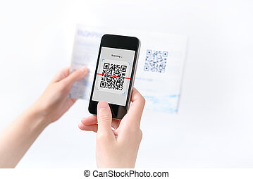 Woman scanning QR code in the magazine on mobile smart...