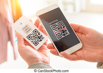 Woman scanning QR code from a label in a shop with mobile...