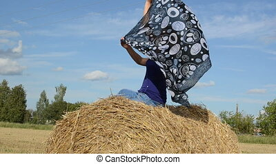 woman scarf straw bale - young blond woman in blue sit on...