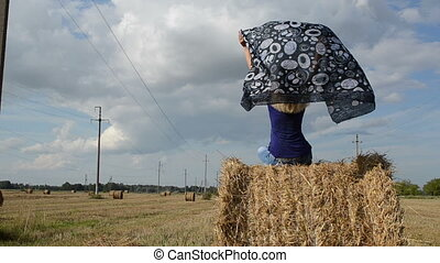 woman scarf straw bale - young blond woman sit on straw bale...
