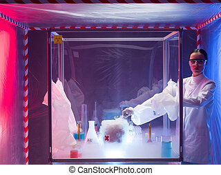 woman scientist conducting experiment with a steaming substance in a protection enclosure, in a containment tent