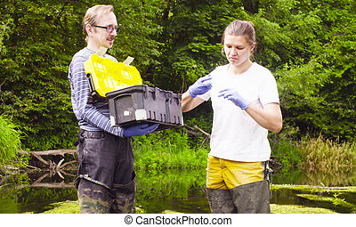 Woman scientist ecologist taking samples of water