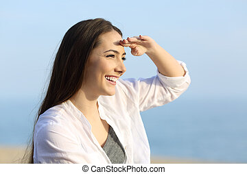 Woman scouting with hand on forehead on the beach