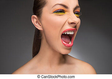 Woman screaming. Furious young women with beautiful make-up shouting and looking away while isolated on grey