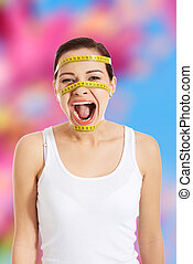 Woman screaming with a measure on her face