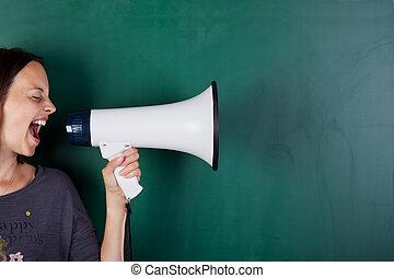 Woman screams into megaphone in front of a blackboard