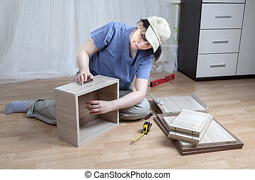 Woman screws to handle drawers, assembly of furniture at home.