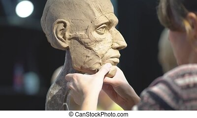 Woman sculptor at work on a sculpture of a human head. The process of restoring the shape of jawbone. Side view. Close up view.
