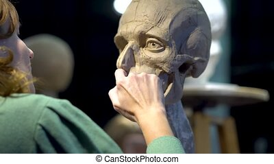 Woman sculptor at work on a sculpture of a human head. The ...