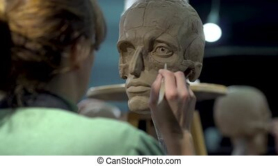 Woman sculptor at work on a sculpture of a human head. The process of restoring the shape of the wings of the nose. Side view. Close up view.