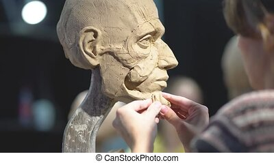 Woman sculptor at work on a sculpture of a human head. The process of restoring the shape of the cheek bone. Side view. Close up view.