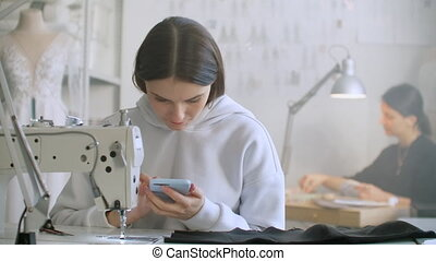 Woman seamstress looks at the smartphone screen in the workplace. Write text messages to customers