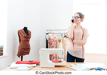 Woman seamstress standing and talking on cell phone in...